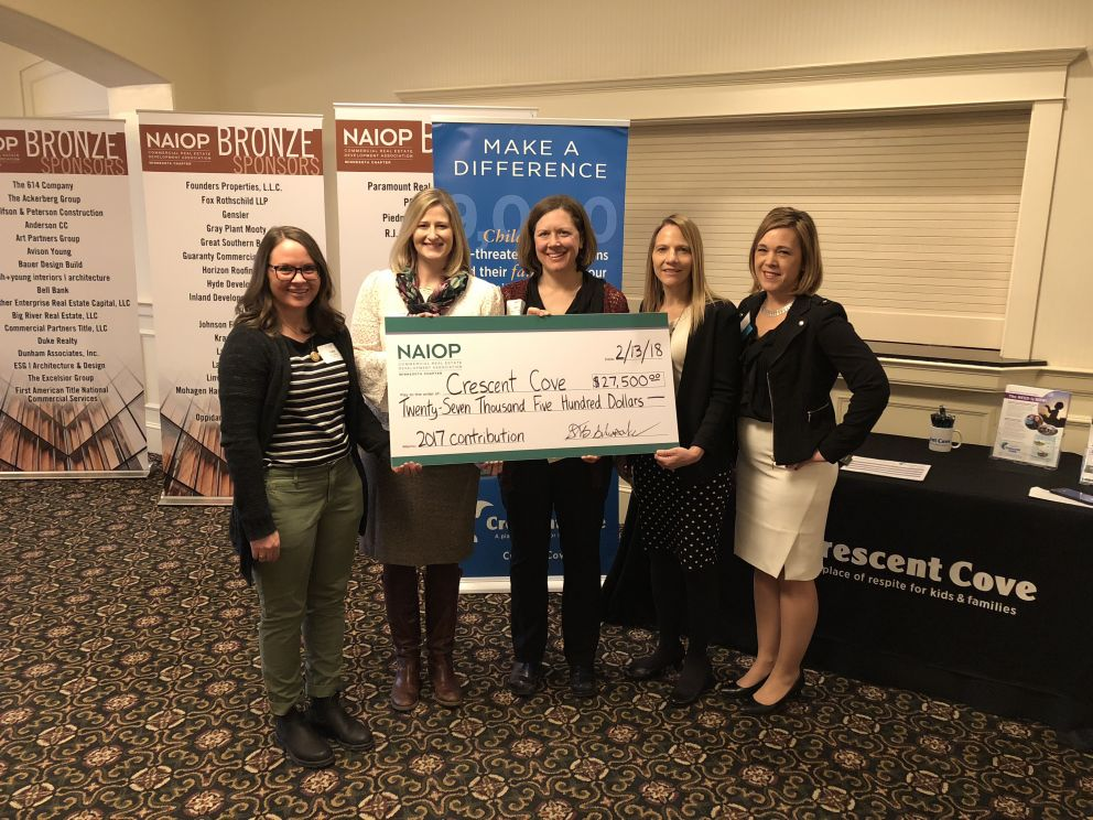 L-R: Katy Glitsos, Tara Anderson, and Katie Lindenfelser of Crescent Cove accept a check from the co-chairs of the Community Enhancement Committee of the Minnesota Chapter of NAIOP, Tami Diehm and Nicole Haapala
